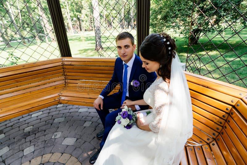 La novia y el novio se sientan en un banco fotografía de archivo