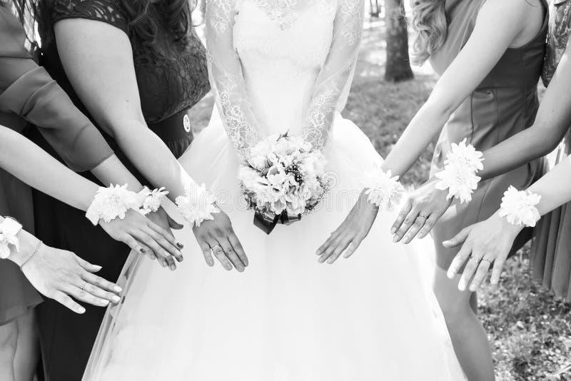 La novia y las damas de honor están mostrando las flores hermosas en sus manos imagen de archivo
