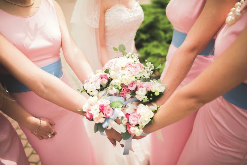 La novia y las damas de honor están mostrando las flores hermosas en sus manos fotos de archivo libres de regalías