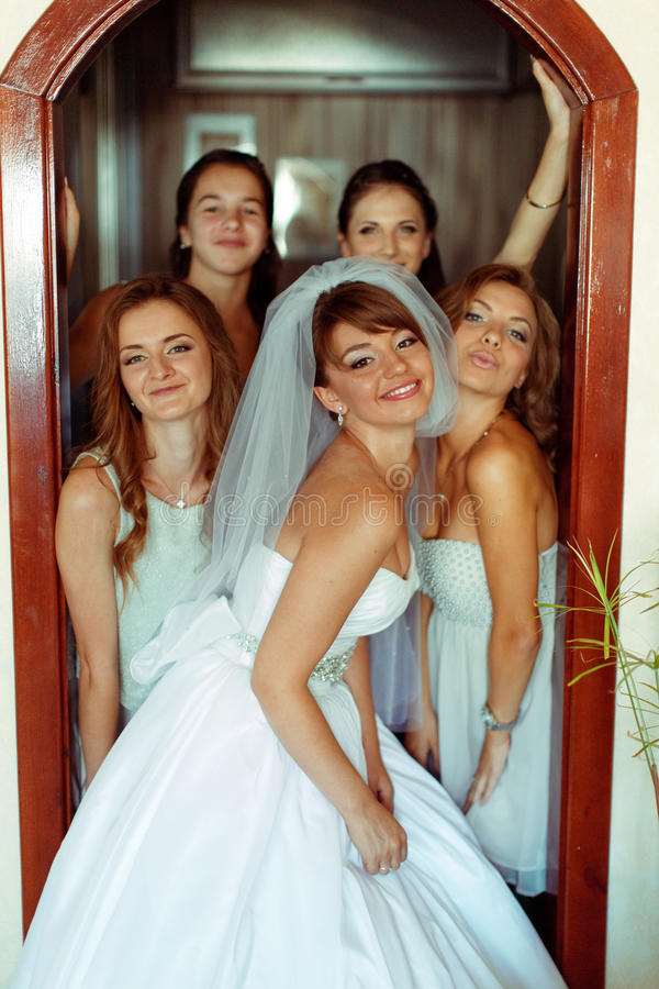 La novia y las damas de honor parecen divertidas mientras que presenta en una puerta abierta foto de archivo libre de regalías