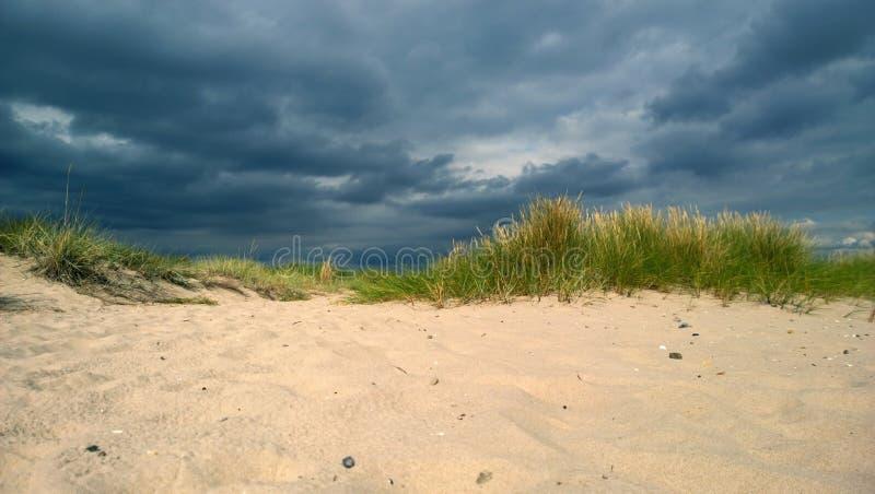 La nube de tormenta inminente en la playa con las dunas y la arena blanca pura imagenes de archivo