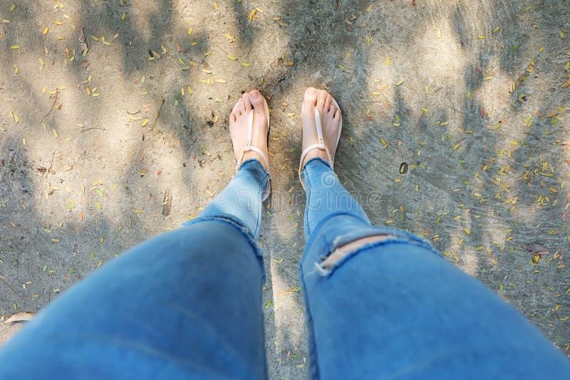 La nudité chausse la femme et les accessoires jaunes de chemise d'ananas Fermez-vous sur des pieds du ` s de fille portant les sa photos stock