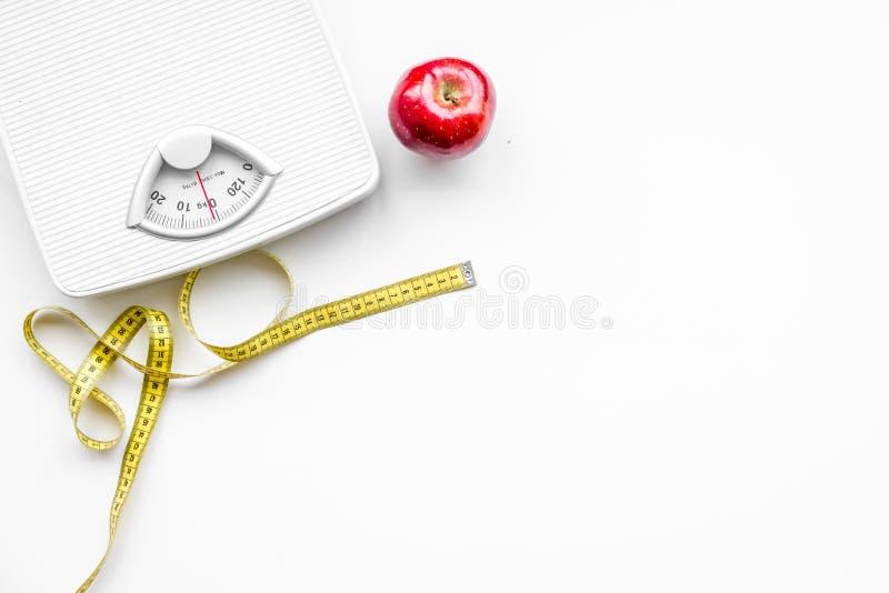 La nutrición apropiada para pierde el peso Escala, cinta métrica, manzana en el espacio blanco de la opinión superior del fondo p fotos de archivo
