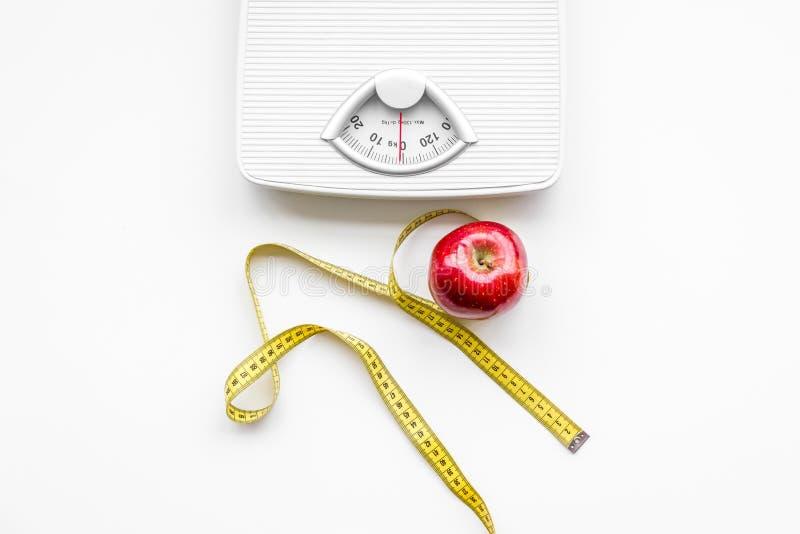 La nutrición apropiada para pierde el peso Escala, cinta métrica, manzana en la opinión superior del fondo blanco fotografía de archivo