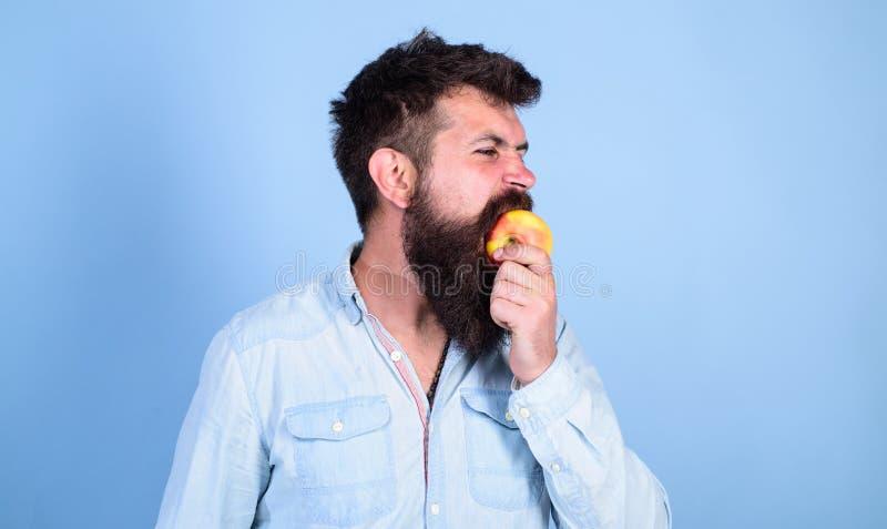 La nutrición de la dieta del hombre come la fruta Sirva al inconformista hermoso con la barba larga que come la manzana Manzana m fotos de archivo