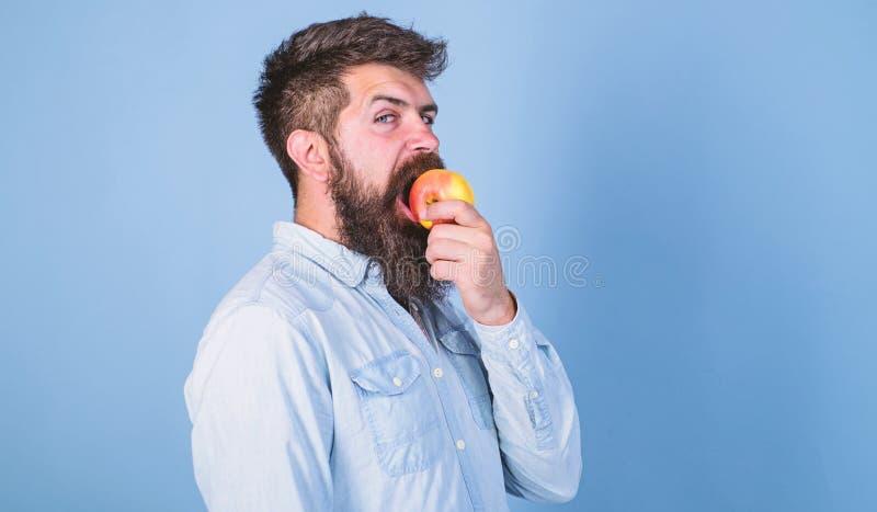 La nutrici?n de la dieta del hombre come la fruta Concepto sano de la nutrici?n Sirva al inconformista hermoso con la barba larga imagenes de archivo