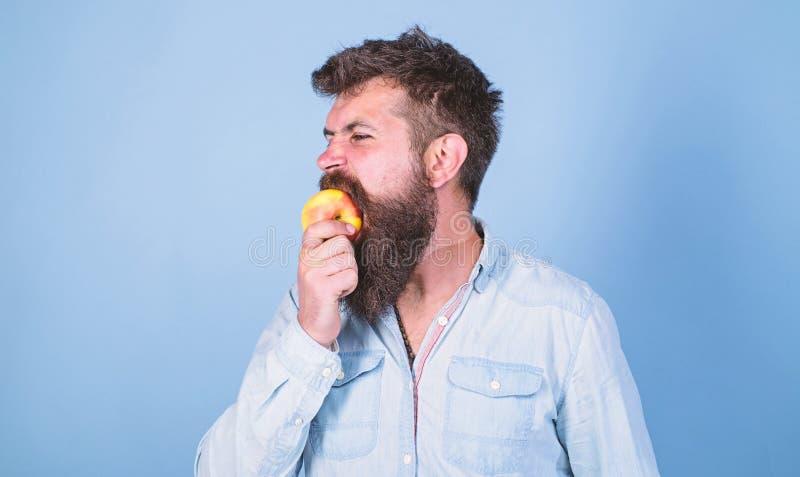 La nutrici?n de la dieta del hombre come la fruta Sirva al inconformista hermoso con la barba larga que come la manzana Manzana m imagen de archivo libre de regalías