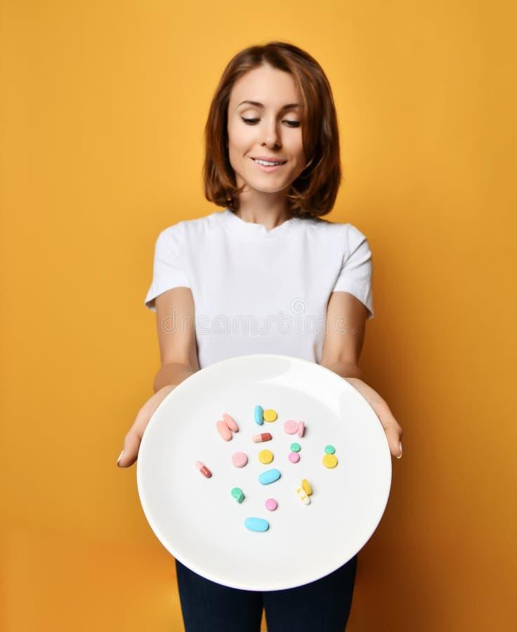 La nutritionniste heureuse et de sourire de femme tient un plat avec la perte de poids différente de prescription de suppléments  photos stock