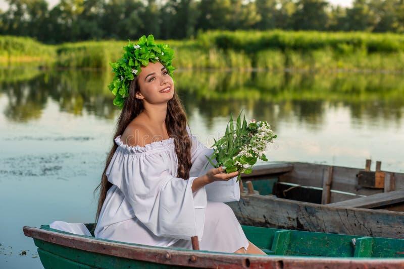 La nymphe avec de longs cheveux foncés dans une robe blanche de cru se reposant dans un bateau au milieu de la rivière photos stock