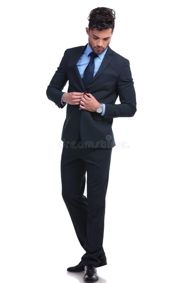La O.N.U del hombre de negocios de moda que abotona su traje y que mira abajo fotografía de archivo