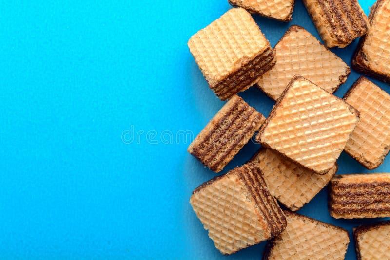 La oblea llenó de crema del cacao en fondo del papel azul fotografía de archivo