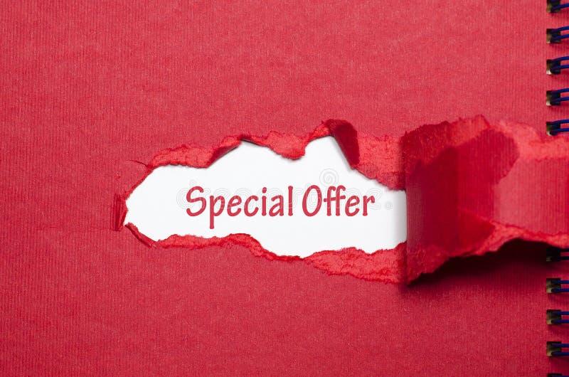 La oferta especial de la palabra que aparece detrás del papel rasgado imagen de archivo