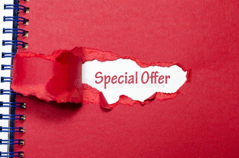 La oferta especial de la palabra que aparece detrás del papel rasgado fotografía de archivo
