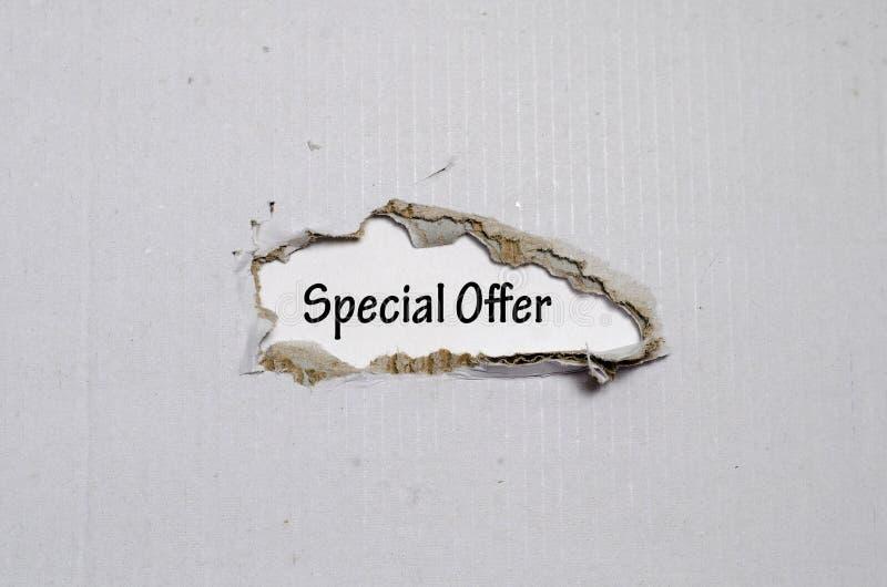 La oferta especial de la palabra que aparece detrás del papel rasgado fotografía de archivo libre de regalías
