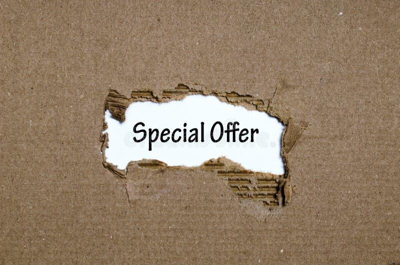La oferta especial de la palabra que aparece detrás del papel rasgado fotos de archivo libres de regalías