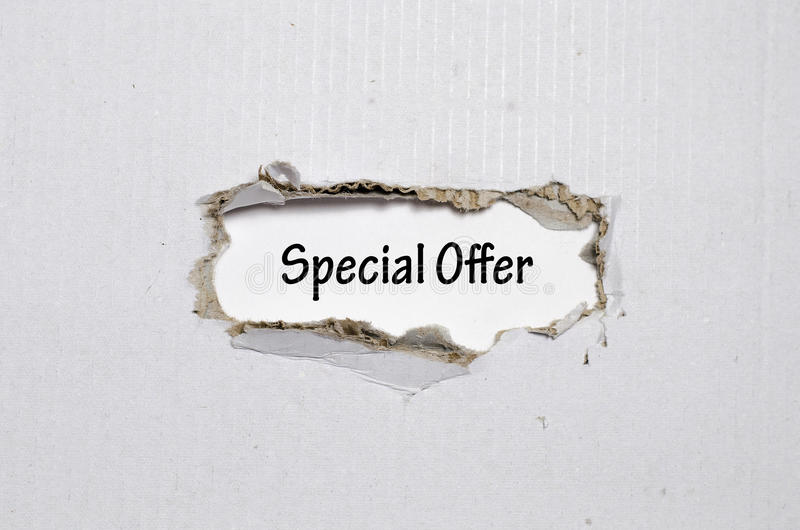 La oferta especial de la palabra que aparece detrás del papel rasgado imágenes de archivo libres de regalías
