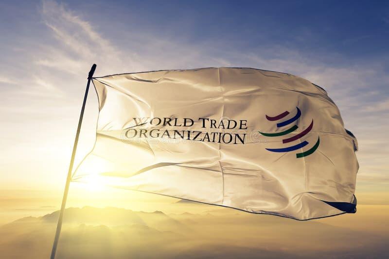 La OMC de la Organización Mundial del Comercio señala la tela del paño por medio de una bandera de la materia textil que agita en stock de ilustración