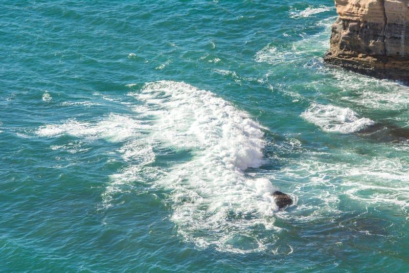 La onda del Océano Índico que rompe la agua de mar en los mares agitados de la orilla rocosa riega espuma y el agua azul en los a fotos de archivo