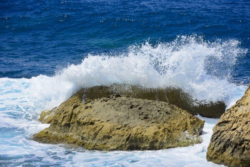 La onda está quebrada en la piedra con un espray imagenes de archivo