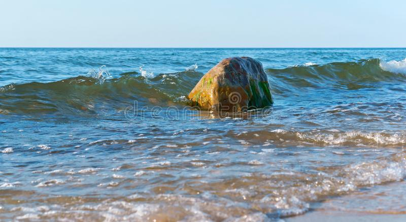 La onda se rompe en una roca, las ondas del mar está batiendo en las rocas en la orilla imagenes de archivo