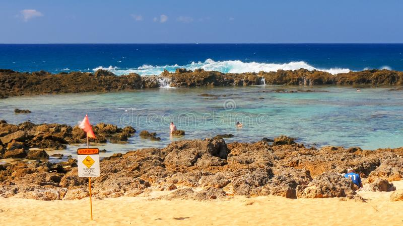 La onda se rompe sobre las rocas y vierte en la piscina de la marea en la ensenada del tiburón fotos de archivo