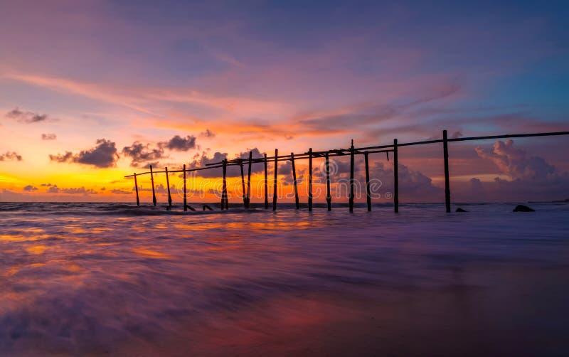 La onda vieja del puente de madera y del mar en la playa en el fondo del cielo de la puesta del sol en Khao Pilai, Phangnga, Tail foto de archivo