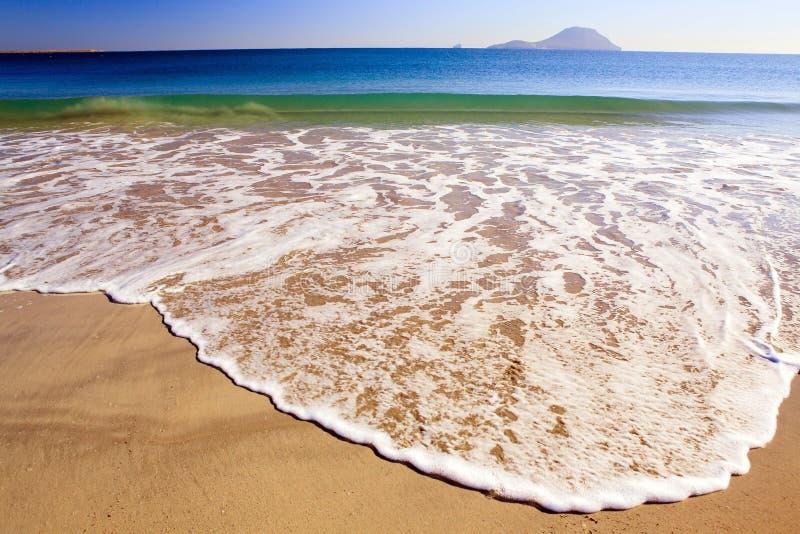La onda y el mar hacen espuma en la arena, playa imagen de archivo