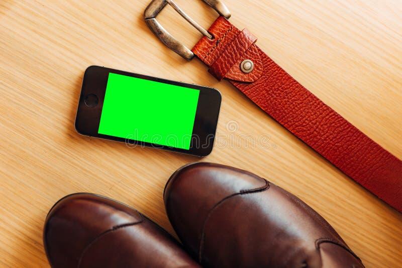La opinión aérea del primer del teléfono elegante blanco con verde aisló la pantalla en la superficie de madera blanca imagenes de archivo