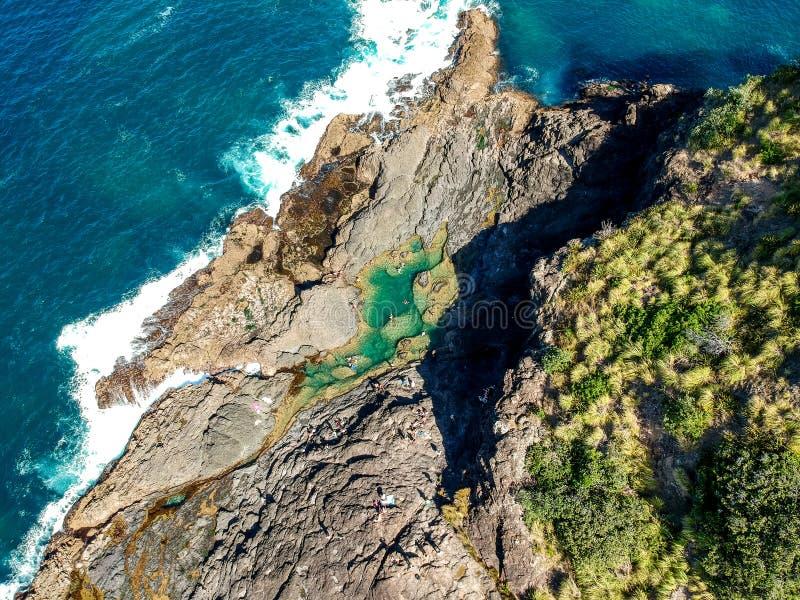 La opinión aérea granangular imponente del abejón de las piscinas de la roca de la sirena y las olas oceánicas en Matapouri aúlla fotos de archivo