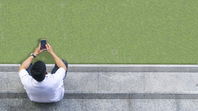 La opinión aérea superior el hombre en la camisa blanca utiliza el teléfono móvil imagen de archivo