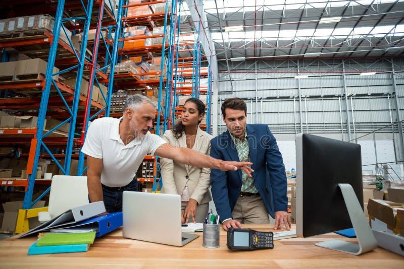 La opinión de ángulo bajo el equipo del trabajador está mirando un ordenador y hablar imagen de archivo libre de regalías
