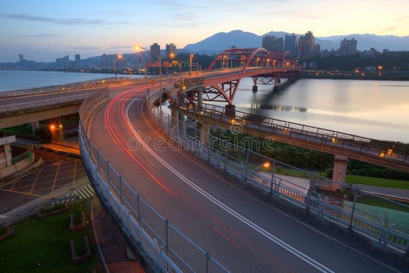 La opinión de la madrugada del coche se arrastra en un puente curvado de la carretera sobre el río hermoso de Tamsui en la ciudad fotos de archivo libres de regalías