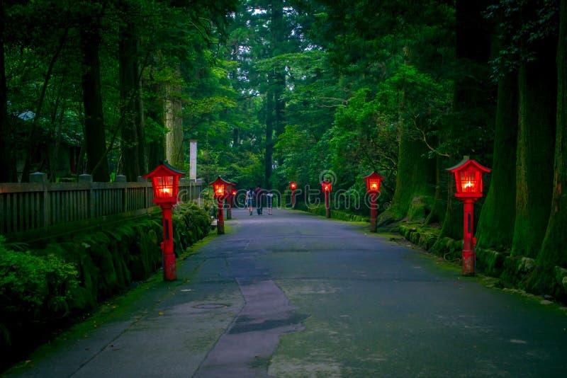 La opinión de la noche del acercamiento a la capilla de Hakone en un bosque del cedro con muchos linterna roja encendida para arr imagen de archivo