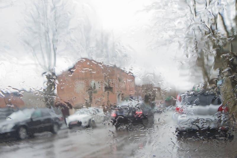 La opinión del camino a través del parabrisas del coche con lluvia cae, conduciendo en lluvia imagen de archivo