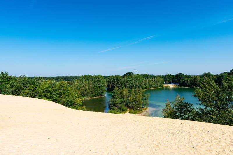 La opinión del panorama del lago cerca de la montaña con el cielo azul y nublado fotos de archivo