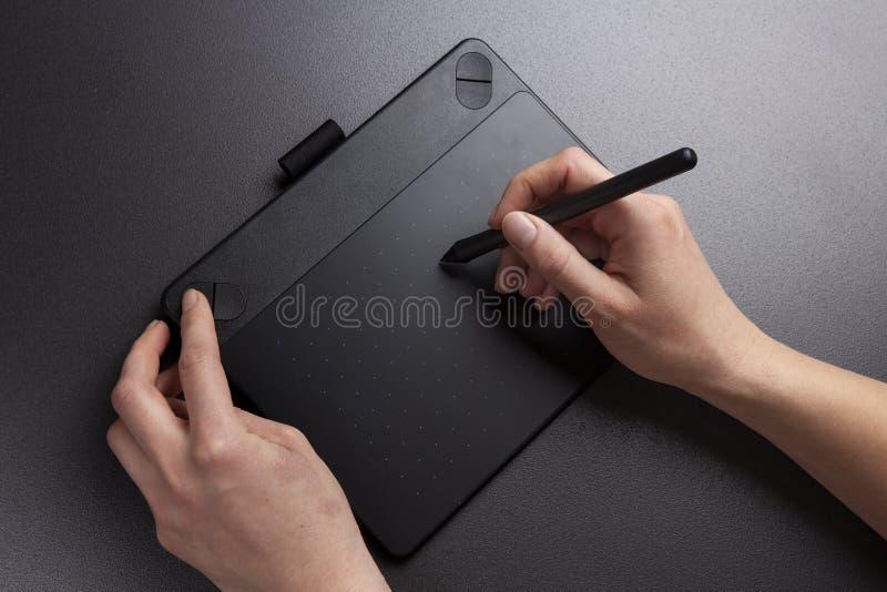 La opinión del primer de las manos del ` s de la muchacha dibuja en superficie de la tableta gráfica Trabajo del diseñador con la fotografía de archivo libre de regalías