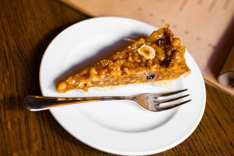 La opinión del primer del pedazo de la torta de miel cubierta con los plátanos y las nueces foto de archivo