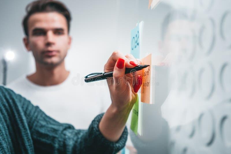 La opinión del primer sobre gente coworking fijó notas sobre una pared de cristal pegajosa de la nota en la oficina fotos de archivo libres de regalías