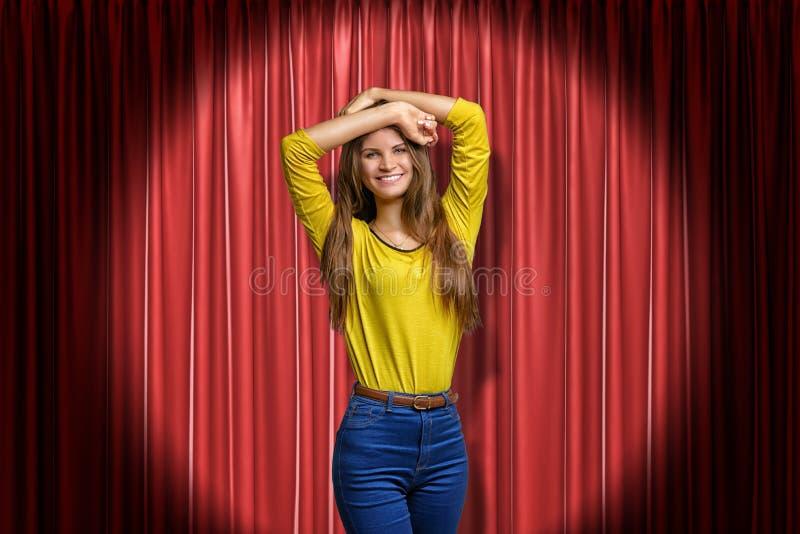 La opinión delantera de la cosecha la muchacha sonriente joven en puente y tejanos amarillos, colocándose en proyector con los br imagen de archivo libre de regalías
