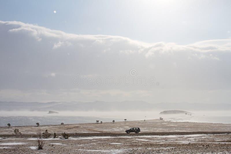 La opinión escénica sobre la orilla del lago Baikal en el invierno y un coche negro monta a lo largo de la costa rocosa imagenes de archivo