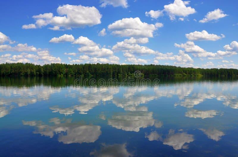 La opinión europea hermosa del paisaje, el bosque y el cielo azul nublado del verano reflejaron en un lago como en el espejo foto de archivo libre de regalías