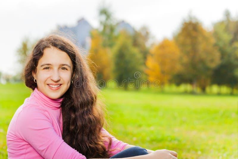 La opinión hermosa del primer de la muchacha se sienta en hierba verde imagen de archivo