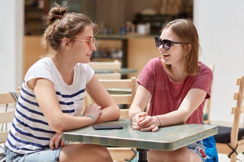 La opinión interior dos muchachas bonitas alegres tiene conversación animada mientras que la espera para la orden en cafetería, d imágenes de archivo libres de regalías