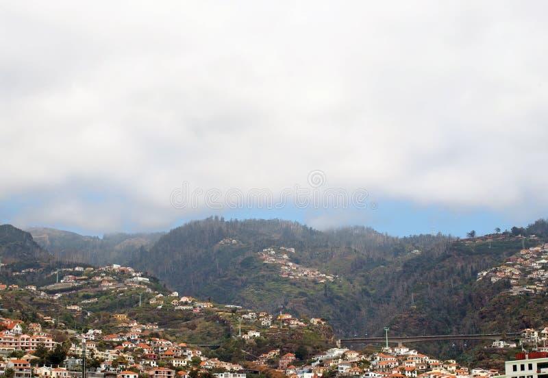 La opinión panorámica aérea del paisaje urbano de la ciudad de Funchal en Madeira con las casas delante del árbol cubrió las mont fotografía de archivo libre de regalías