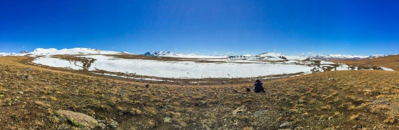 La opinión panorámica un hombre que se sienta solamente en el Deosai aclara el parque nacional, tierra cubierta por la nieve imagenes de archivo