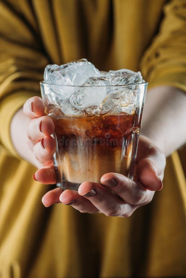 la opinión parcial la mujer que llevaba a cabo el vidrio de frío preparó el café con los cubos de hielo en manos fotografía de archivo libre de regalías
