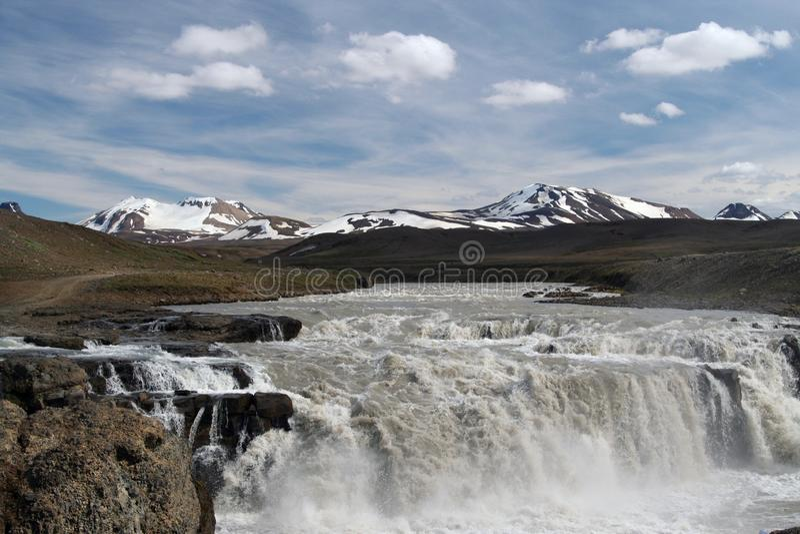 La opinión sobre la cascada en paisaje seco estéril árido con nieve capsuló en parte las montañas en el horizonte - Islandia foto de archivo libre de regalías