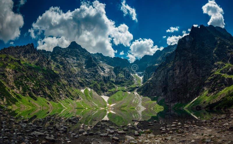 La opinión sobre el lago llamó la charca negra debajo de las montañas altas y rocosas fotos de archivo libres de regalías