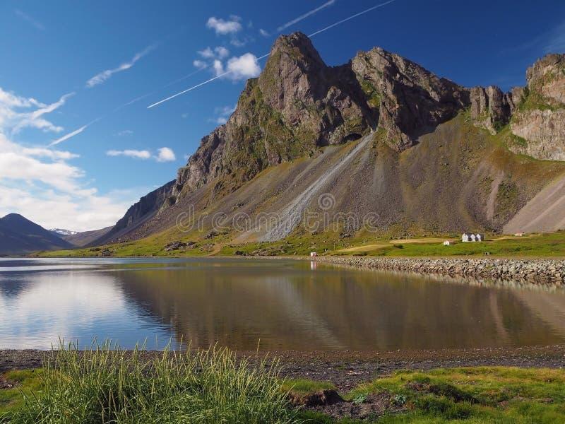 La opinión sobre hierba verde de las montañas y el lago del mar en los fiordos del este hielan foto de archivo