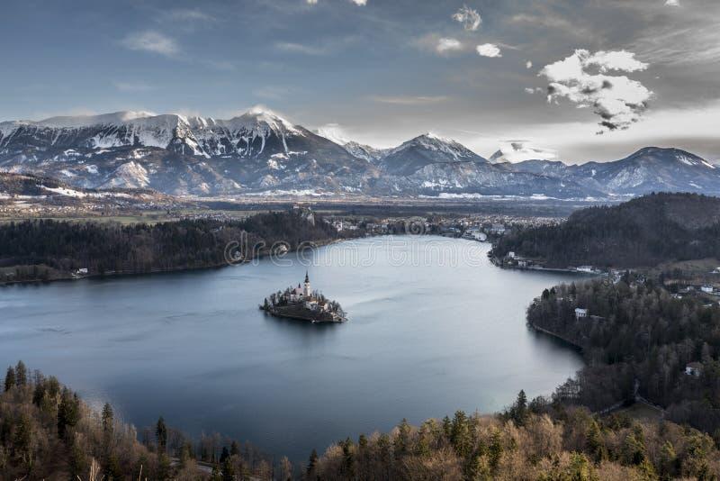 La opinión sobre la isla con la iglesia en el medio del lago sangró entre las montañas en nieve imagen de archivo